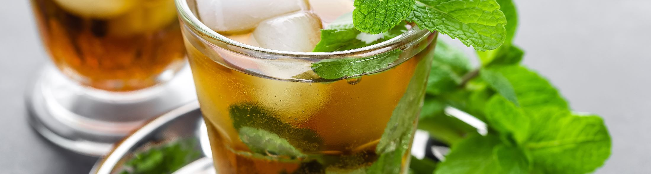 Glasses of mint juleps with fresh mint on top and on the side of the glass